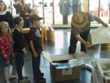 a park ranger distributes supplies to children in a neat line