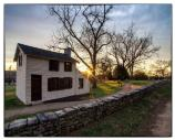 Small white historic house beside stone retaining wall along the Sunken Road