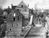 Confederate soldiers standing on the west side of the damaged railroad bridge at Fredericksburg. To the left is the Marye Mill. In the background is Marye's Heights. Detailed as a photographer, Russell was impeded with the Union army at Fredericksburg. On this occasion his purpose was to photograph the bridge prior to the 1863 spring campaign so that engineers would know how to rebuild the bridge if necessary.
