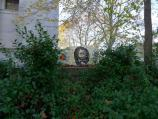 A mural of the face of Ulysses S. Grant is visible through bushes, with the tomb behind.