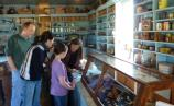 A family looks at goods for sale in a store with a long glass case in front and well-stocked shelves on the walls.