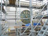 Color photo of a new clock face visible through scaffolding.