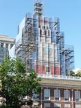 Color photo of a brick building with a decorative scrim masking scaffolding around the tower.