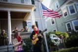 A girl sings while a man play guitar in front of the John F. Kennedy National Historic Site