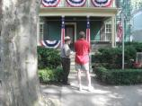 Ranger and visitor in front of house with bunting.l
