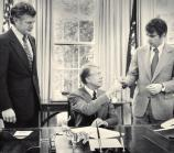Three men in suits getting ready to sign a piece of paper