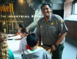 A male ranger looking at camera smiling while assisting kids at a craft table.