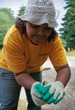 A female student holds a small frog she found while doing maintenance work