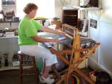 Museum volunteer demonstrates weaving loom.
