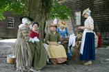 Colonial women at Hartwell Tavern participating in a spinning bee