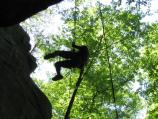 person hanging on a rope next to a cliff face