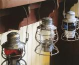 three old railroad lanterns hanging under a shelf