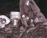 black and white photo of miner's lunch bucket, hat, light, and tools