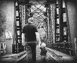 black and white photo of father and sun walking near train bridge