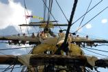 National Park Service volunteers demonstrate how to furl a sail on board the replica tall ship Friendship