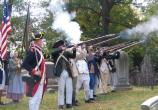 A group of re-enactors fire a volley in remembrance of the soldiers who died during the Battle of Pell's Point and are buried in the cemetery at St. Paul's Church National Historic Site