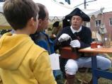 A re-enactor demonstrates how to create a quill pen from a goose feather during the Battle of Pell's Point Encampment at St. Paul's Church NHS.