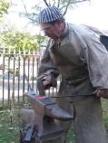 A professional blacksmith takes his profession back in time during the Battle of Pell's Point Encampment at St. Paul's Church NHS. The blacksmith is demonstrating how a nail would have been made by hand using a forge, hammer and anvil.