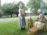 Two female re-enactors chat as one spins wool into yarn during Colonial Day at St. Paul's Church NHS.