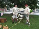 A re-enactor dressed in 18th-century style clothing talks to a man dressed in modern clothes about life during the Colonial era.