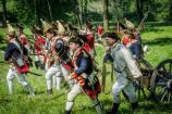 Several British Revolutionary War soldiers moving quickly across a field.