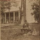 Aged photo of 2-story house with columned front and a few trees, a man in tophat, two kids, and a dog.