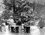 Herbert & Lou Henry Hoover seated on porch.
