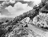 Visitors enjoy the views along Skyline Drive. Clouds and rocky cliffs frame the visitors and the Drive as it winds through the mountains.