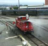 Lehigh Valley caboose #95003 being pressure-washed by a paint contractor.