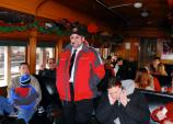 Steamtown VIP Bob Patterson leads guests in a holiday sing-along aboard a