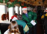 VIP Connie Arbochus distributes holiday song books aboard a