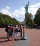 Several visitors join a park ranger behind the Statue of Liberty.