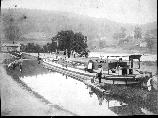 "This photograph of a boat at Lock 72 below Lackawaxen shows the boat being ""snubbed"" by the captain. Snubbing was the process of tying the boat to a ""snubbing post"" and thereby halting its forward motion. Also note the plants growing on top of the cabin. As the families considered the boats home for the summer these were likely vegetables grown for food. Also on the left side note the man and boy on either side of the lock. These people were called lock tenders."