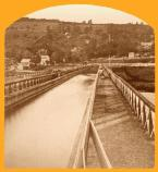 This photograph shows a view down the Delaware Aqueduct. With a six foot head of water and width at waterline of twenty feet the aqueduct allowed the passage of even the largest of 140 ton boats the D & H had in service. The ultimate strength of Roebling's 8 ½ cables was 3,870 tons. It is interesting and amazing to note that a one foot section of the cable weighed 133 lbs with its wire wrapping! The strength of the wire was 90,000 lbs per superficial inch!
