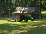 Park employee mowing grass near one of the reconstructed soldier cabins.