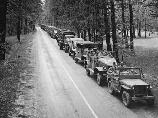 large convoy of jeeps and army trucks along road; B&W