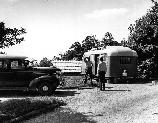 Two men stand facing each other along the roadside between a trailer and an automobile