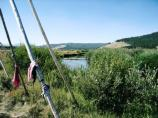 Scarves are tied around wooden poles near a creek, bordered by low vegetation and rolling hills.