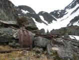 Rusting ironwork sits among boulders with snowy mountains in the background.