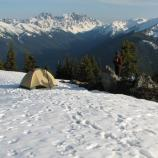 A cream colored tent sits on a snow packed ridge with large mountains in the background.
