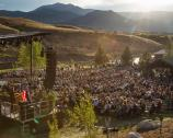 A crowd sits at an amphitheatre for a concert on the 100th birthday of the National Park Service at Yellowstone.
