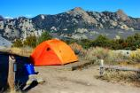 Campsite 15 with orange tent and distant scenic view of City of Rocks