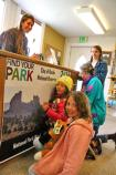 Young park visitors sign their name to a Centennial poster
