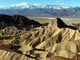 Snow covered Panamint Mountains contrast with the warm earth tones of Manly Beacon and the badlands.
