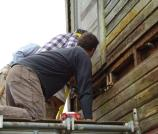 Scott Swenson at the Kineth Water Tower removing historic siding and checking for rot.
