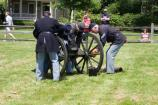 Staff and volunteers in period clothing assemble the mountain howitzer as part of a special program on the park's Parade Ground.