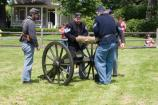 Staff and volunteers in period clothing ensure that the howitzer's barrel is carefully placed on top of the carriage and secured before firing.