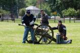 Members of the howitzer crew begin the drill to prepare, load, and fire the howitzer.