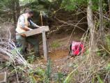 NCRI Archaeologist Beth Horton screens for artifacts in rough terrain at Lewis and Clark National Historical Park