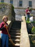 Volunteers help clean the areas surrounding the stairs and raised beds near the old Officer's Quarters.
